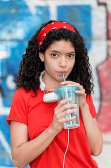 Garota de frente para beber água