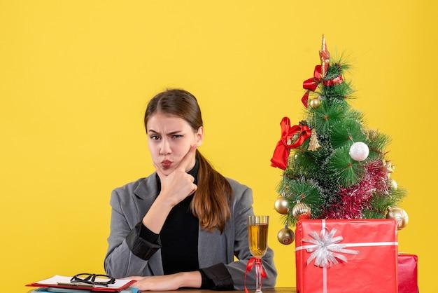 Garota de frente para pensar sentada na mesa, árvore de natal e presentes