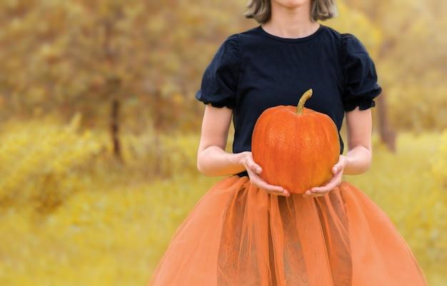 Garota de fundo de halloween segurando uma abóbora nas mãos