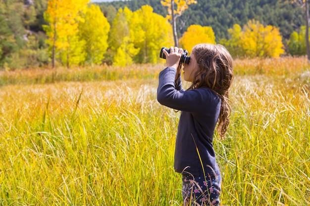 Garota de garoto binocuar explorer na natureza outono amarelo