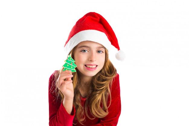 Garota de garoto de natal segurando biscoito de árvore de natal