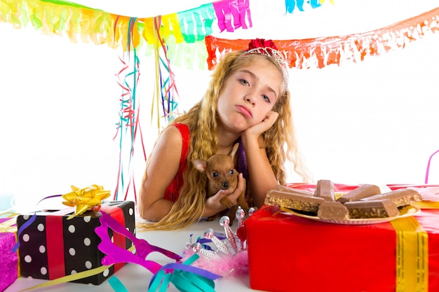 Garota de garoto loiro de gesto entediado em festa com cachorro