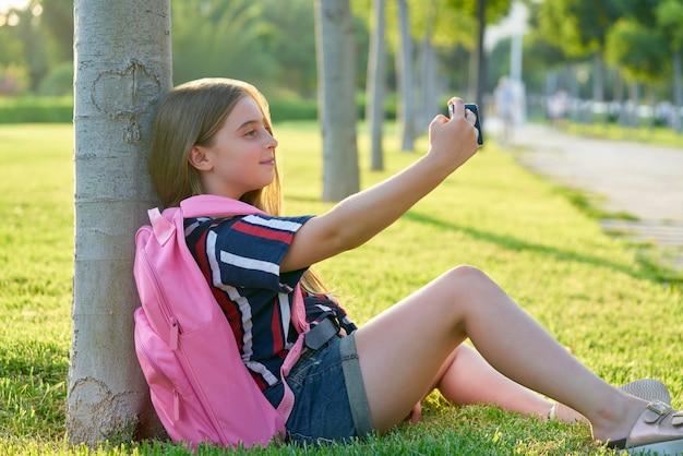 Garota de garoto loiro estudante com smartphone no parque