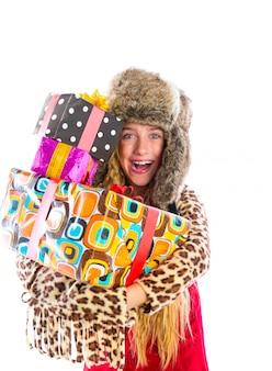 Garota de garoto loiro inverno com presentes empilhados sorrindo