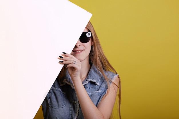 Garota de gengibre de óculos de sol se esconde para pintura branca sobre fundo amarelo