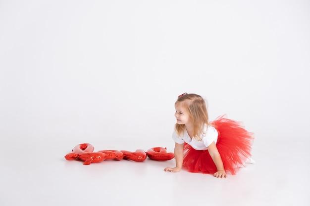 Garota de giro da criança com o amor de inscrição de balões em um fundo branco. dia dos namorados.