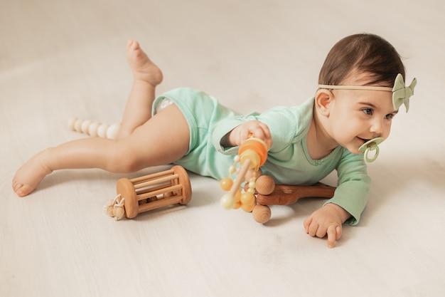 Garota de giro da criança de 8 meses encontra-se no piso de madeira da casa brincando com brinquedos de desenvolvimento de madeira. foto de alta qualidade