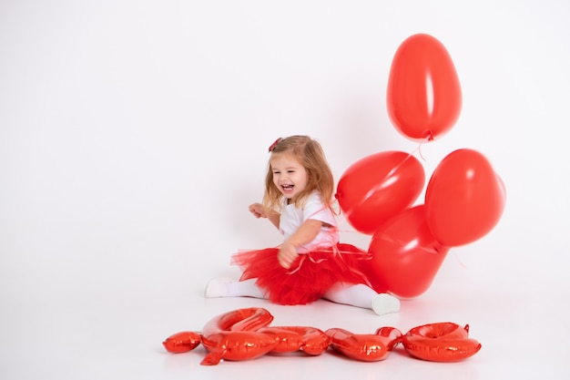 Garota de giro da criança segurando balões de coração com amor de inscrição de balões em um fundo branco.