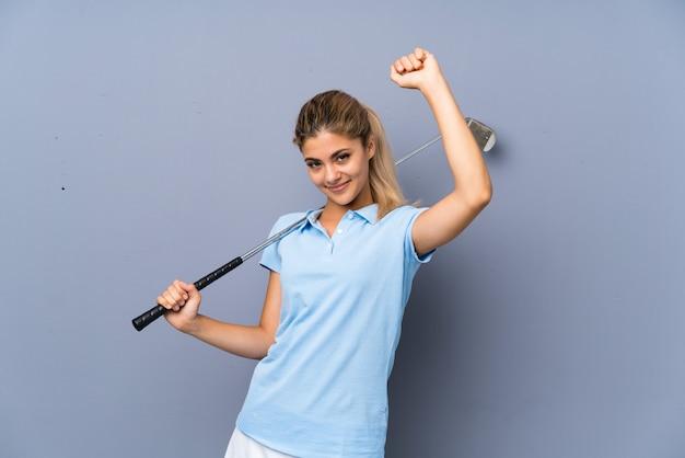 Garota de golfista adolescente sobre parede cinza, celebrando uma vitória