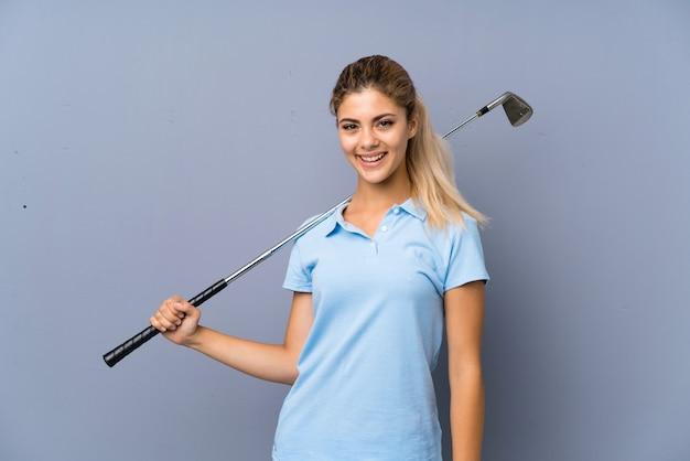 Garota de golfista adolescente sobre parede cinza