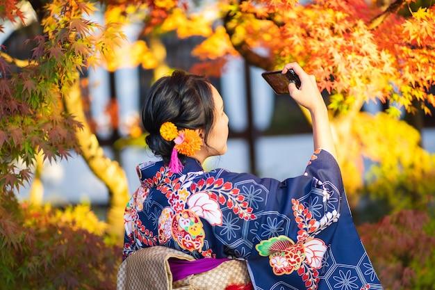 Garota de gueixas vestindo quimono japonês entre o portão de madeira vermelho tori