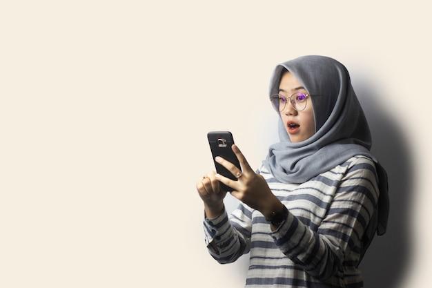 Garota de hijab surpresa surpresa olhando para um telefone celular
