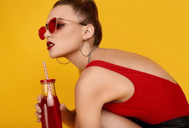 Garota de hipster glamour elegante em top vermelho, calção preto com bebida cocktail