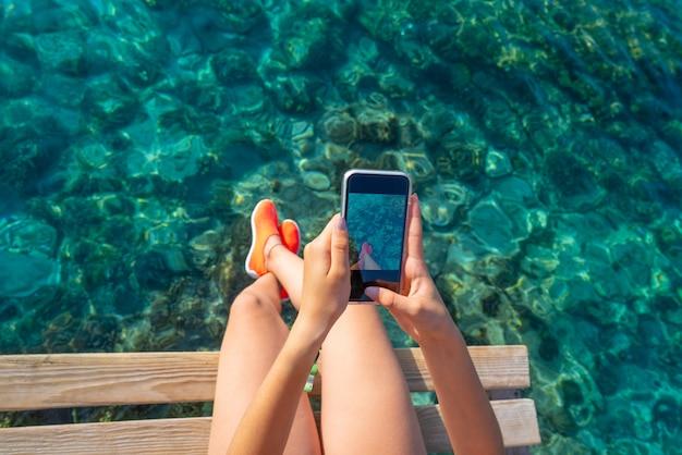 Garota de ibiza tirando fotos do smartphone