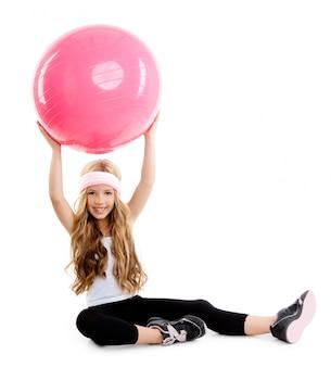Garota de ioga de crianças de ginásio com bola rosa de pilates