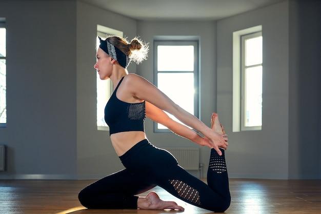 Garota de ioga de manhã fazendo exercícios de alongamento na sala de pilates.