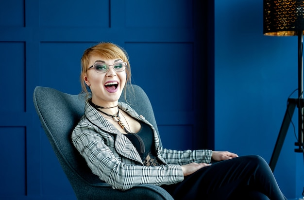 Garota de jaqueta e óculos se senta em uma cadeira e grita com a equipe