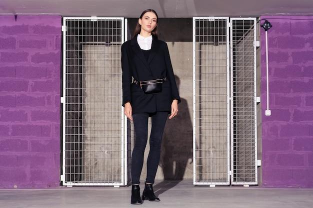 Garota de jaqueta preta e calça jeans em pé perto da sala tecnológica com porta de grade de metal