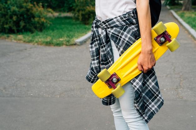 Garota de jeans e uma camisa xadrez está andando no parque com skate de plástico amarelo nas mãos