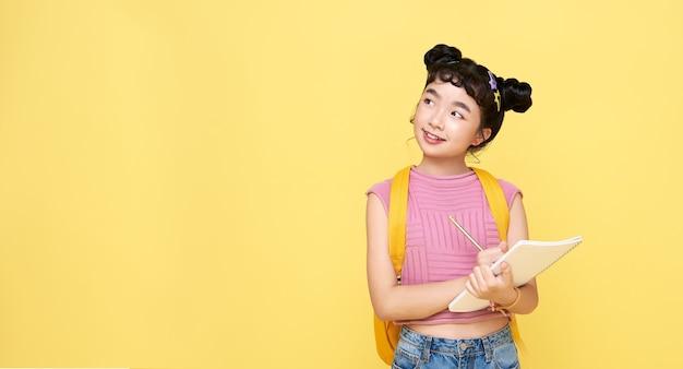 Garota de jovem criança asiática pensando e escrevendo algo no caderno isolado em fundo amarelo.