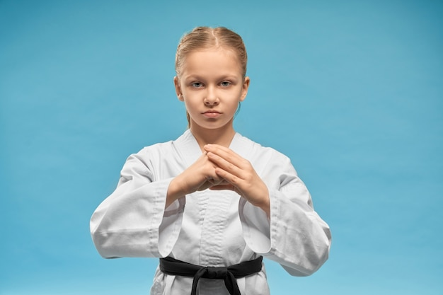 Garota de karatê com faixa preta, praticando a posição de mãos.