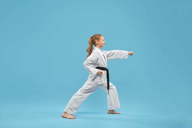 Garota de karatê com faixa preta praticando artes marciais.