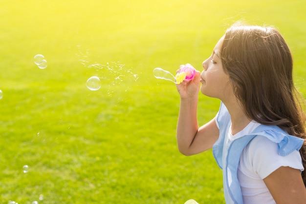 Garota de lado fazendo bolhas de sabão lá fora
