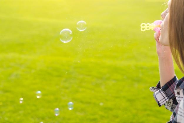 Garota de lado fazendo bolhas de sabão