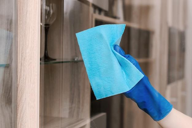 Garota de luvas azuis limpa o vidro com um pano