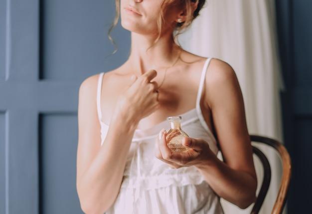 Garota de manhã usa um perfume em volta do pescoço