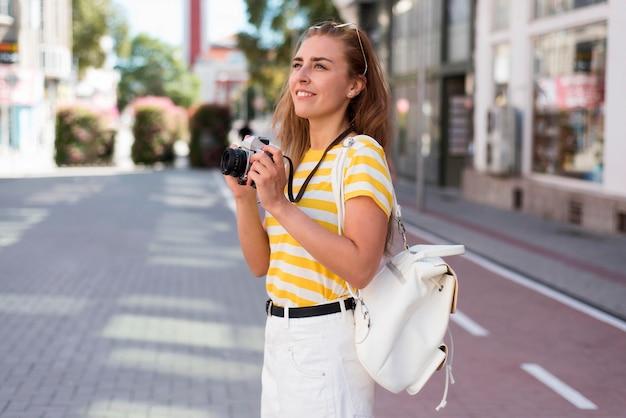 Garota de meio tiro com câmera na cidade