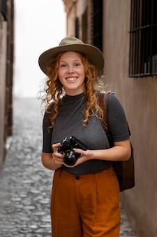 Garota de meio tiro com chapéu e câmera