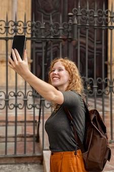 Garota de meio tiro tirando uma selfie na frente do prédio