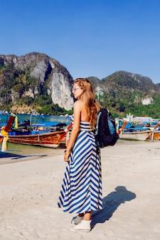 Garota de mochileiro muito bronzeado posando na ilha tropical quente de phi phi, uma vista incrível sobre montanhas e barcos locais.