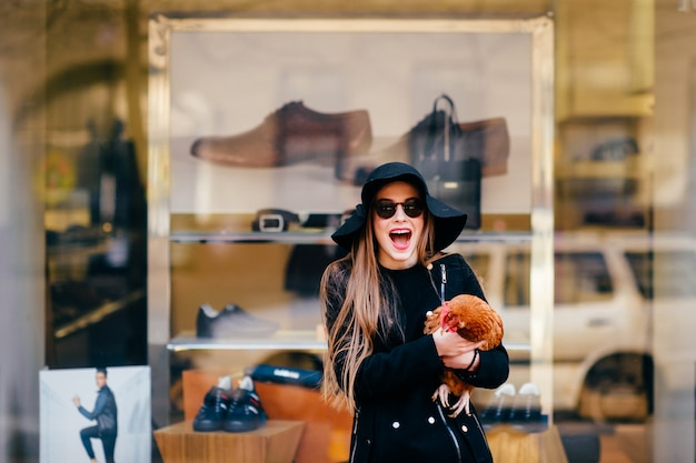 Garota de moda bizzare animado segurando o frango nas mãos na grelha da vitrine de botique.