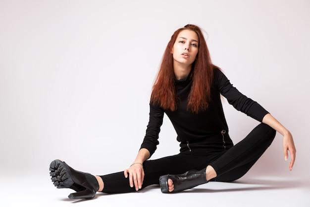 Garota de modelo de alta moda em uma gola alta preta e calça jeans em branco