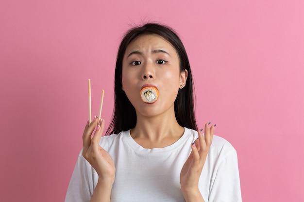 Garota de modelo de beleza asiática comendo sushi roll, comida japonesa saudável. linda mulher segurando pauzinhos com rolo de filadélfia