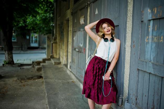 Garota de modelo loira elegante e bonita em elegante saia de veludo vermelho de veludo, blusa branca e chapéu, posou com telefone e fones de ouvido.