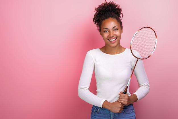 Garota de mulato desportivo permanente com raquete de badminton
