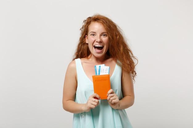 Garota de mulher jovem ruiva animado em roupas leves casuais posando isolado no fundo branco, retrato de estúdio. conceito de estilo de vida de pessoas. simule o espaço da cópia. com passaporte, cartão de embarque, passagem.