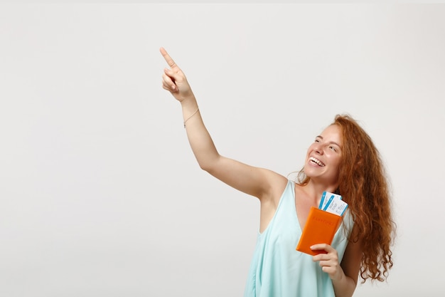Garota de mulher jovem ruiva em roupas leves casuais posando isolado no fundo branco. conceito de estilo de vida de pessoas. simule o espaço da cópia. segurando o passaporte, o cartão de embarque, a passagem, apontando o dedo indicador para cima.