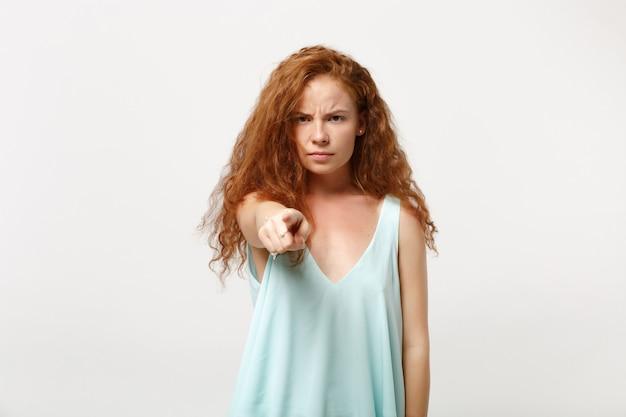 Garota de mulher jovem ruiva insatisfeita em roupas leves casuais posando isolado no fundo da parede branca, retrato de estúdio. conceito de estilo de vida de pessoas. simule o espaço da cópia. apontando o dedo indicador na câmera.
