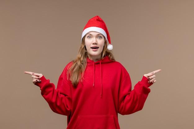 Garota de natal com cara animada em fundo marrom mulher férias natal emoção