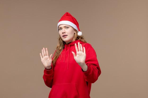 Garota de natal com rosto confuso em fundo marrom, férias natalinas, vista frontal
