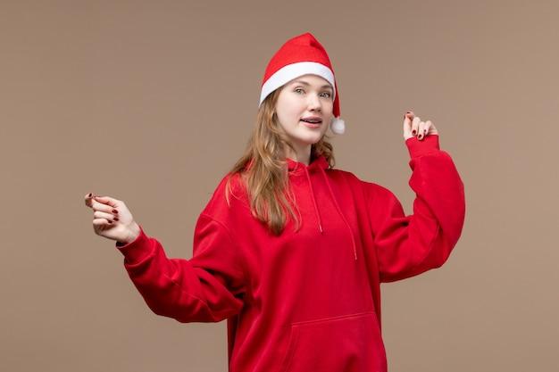 Garota de natal dançando em fundo marrom, vista frontal, mulher, feriado, natal