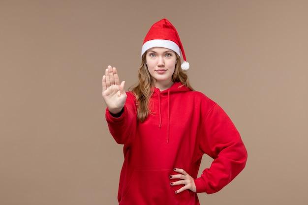 Garota de natal de frente pedindo para parar no modelo de fundo marrom feriado natal