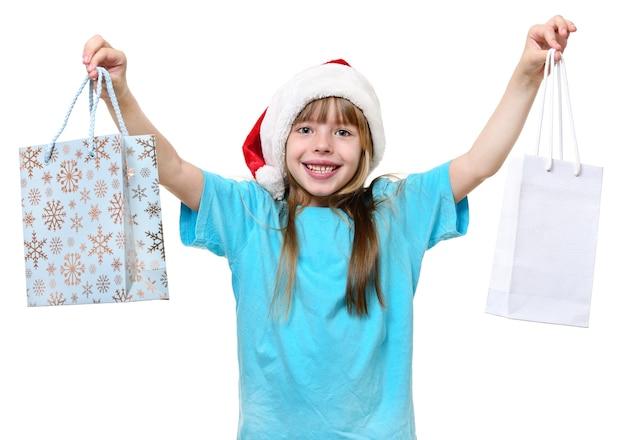 Garota de natal feliz segurar grandes sacolas de compras isoladas em branco.