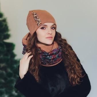 Garota de natal usando chapéu de malha quente e luvas, isoladas em cinza