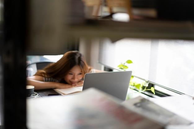 Garota de negócios asiáticos começar a trabalhar com o computador portátil no café