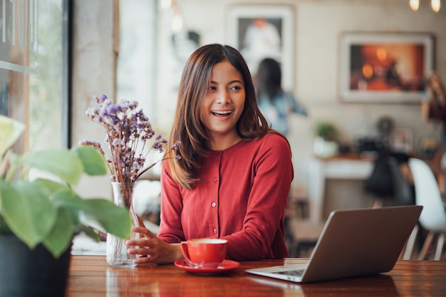 Garota de negócios asiáticos trabalhando e bebendo café no café com laptop